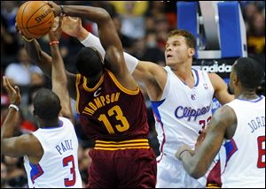Los Angeles Clippers forward Blake Griffin (32) and guard Chris Paul (3) defend Cleveland Cavaliers forward Tristan Thompson (13) during the first half of an NBA basketball game in Los Angeles.