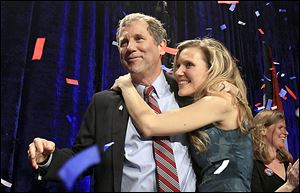 Sen. Sherrod Brown is hugged by his daughter, Liz,  as they celebrate his re-election Tuesday night. Mr. Brown called his victory a triumph for the middle class.