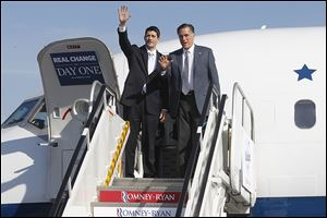 Republican presidential candidate, former Mass. Gov. Mitt Romney and his running mate Rep. Paul Ryan (R., Wis.), wave as they exit a campaign charter airplane at Cleveland Hopkins International airport.