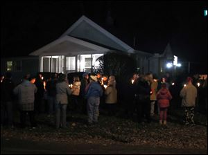 Family and friends attend a candlelight vigil for Katie Walton-Sheppard, who was murdered by her husband at her Rivard Rd. home in Toledo.