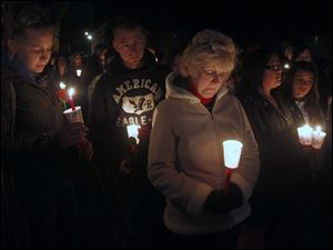 Family and friends hold candles.