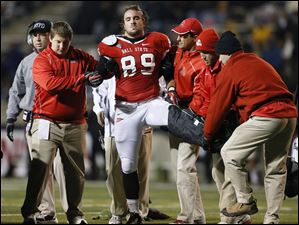Ball State tight end David Schneider (89) is helped off the field after injury against the University of Toledo.
