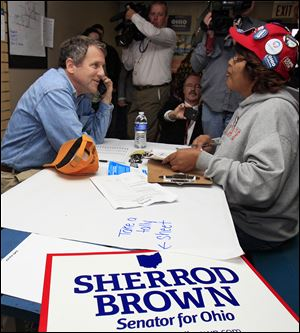 Sen. Sherrod Brown, along with volunteer Shirley Sherman, calls campaign workers on Tuesday to thank them for their service at a campaign office in Columbus.
