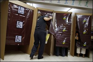 A voter enters a voting booth during elections in San Juan, Puerto Rico Tuesday.