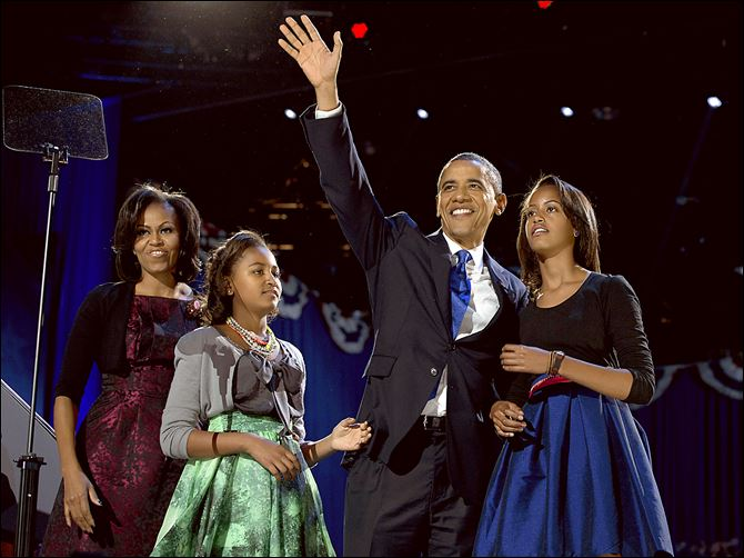 07n4fam President Barack Obama waves as he walks on stage with first lady Michelle Obama and daughters Malia and Sasha at his election night party Wednesday, Nov. 7, 2012, in Chicago. Obama defeated Republican challenger former Massachusetts Gov. Mitt Romney. (AP Photo/Carolyn Kaster)