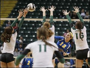 St. Ursula Academy player Lauren Daudelin, 12, tries to spike the ball past the defense of Cincinnati Ursuline.