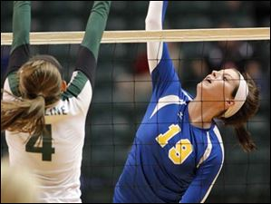 Toledo St. Ursula Academy player Maddie Burnham, 19, kills the ball past Cincinnati Ursuline player Abby Weisenburger, 4.