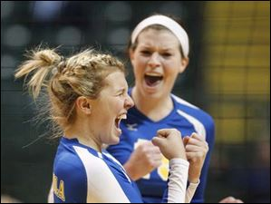 Toledo St. Ursula Academy players Ryann Cox, 4, and Maddie Burnham, 19, celebrate a point early in the fourth set.