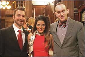 From left, Joshua Cooper, Negar Cooper, center, and Tim Hanson, right, pose for a photograph Friday evening during the Sapphire Blues to Benefit the Toledo Opera at the Toledo Club in Toledo.