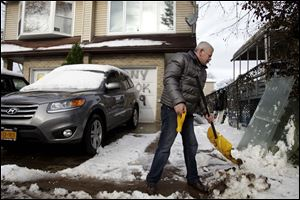 Gennady Naydis keeps clearing his driveway even as the handle breaks off his shovel in the New Dorp section of Staten Island, N.Y., Thursday.
