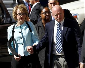 Former Democratic Rep. Gabrielle Giffords, left, and her husband Mark Kelly leave after the sentencing of Jared Loughner, in back of U.S. District Court Thursday in Tucson, Ariz.