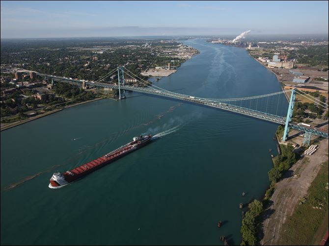 A freighter passes the Ambassador Bridge that links Detroit on the right and Windsor on the left. A new Canadian-financed bridge linking the cities could create thousands of jobs.
