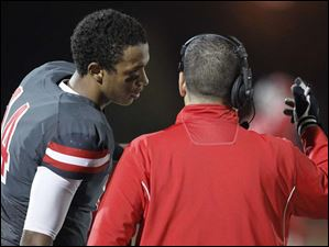Central Catholic High School quarterback Deshone Kiser speaks with head coach Greg Dempsey.