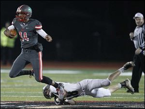 Central Catholic High School quarterback Deshone Kizer, 14, gets away from Mansfield Madison High School player Seth Gowitzka, 48.