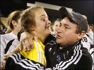 Perrysburg co-head coach Jorge Diaz hugs goalie Chloe Buehler.