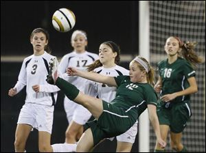 Mason's Jenn Williams (12) kicks the ball against Perrysburg's Kathryn Weber (10).