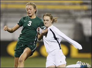 Perrysburg's Lucy Watson (4) moves the ball against  Mason's Alex Niehoff (3).