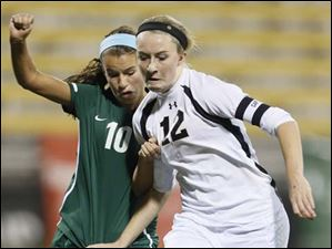 Perrysburg's Maddy Williams (12) charges to the net against  Mason's Olivia Gaus (10).
