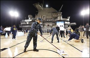 Military personnel and volunteers wipe off condensation in an attempt to dry the damp court before the start of the game between Ohio Sate and Marquette aboard the USS Yorktown. Officials called off the game because of the damp court.