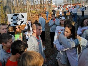 Members of the boys soccer team receive sendoff cheers and hugs from fellow students, including Catie Sack, 17, right.