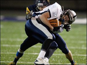 Whitmer High School player Devon Miller, 27, tackles Hudson High School player Colton Whited.