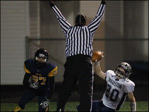 Hudson High School player Tim Kennedy, 20, scores a touchdown against Whitmer High School player Devon Miller, 27.