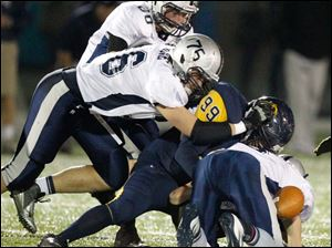 Whitmer High School player Robert Vargus, 99, forces Hudson High School quarterback Mitchell Guadagni, 6, to fumble the ball.
