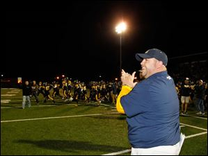 Whitmer High School head coach Jerry Bell applauds his team after they defeat Hudson High School.