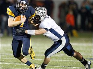 Whitmer quarterback Nick Holley, 7, is tackled by Hudson's Ben Hart.