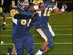 Whitmer's Dylan Bovia, 67, and Tre Reditt-Sterrit, 12, celebrate after Reditt-Sterrit scores a touchdown.