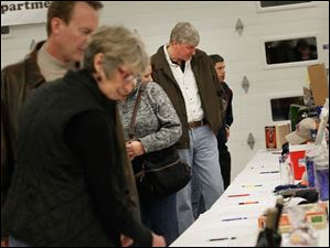 Bill Hayes, of Perrysburg, second from right, took a look at the silent auction times available.