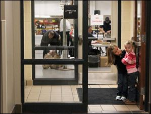 Ella Recker, 5, left, and Kylie Pennington, 3, right, keep an eye on the entrance.