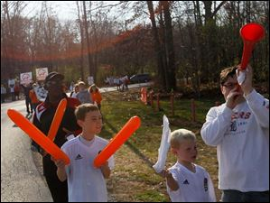 Josh Pawlicki, 10, center, and his bother Tyler, 7, join their father, Robert, right, in cheering.