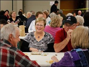 Kathy Weaver, of Maumee, center, and her husband Ken, center right, talk with Gary Hickman, of Perrysburg, left, and his wife Bonnie, right, over a game of bingo.