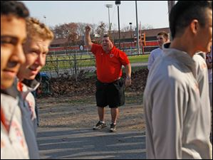Tony Turley, center, cheered for the boys soccer team as they passed him.