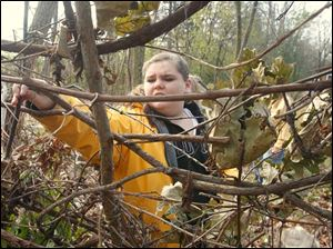 Pemberville resident and Girl Scout Solana Lopez learns how to make a squirrel's nest at the WW Knight Nature Preserve in Perrysburg, Ohio. She is adding sticks to a large nest in the backyard of the activity building.