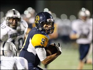 Whitmer High School player Christopher Boykin, 9, catches a pass for a first down in the fourth quarter.