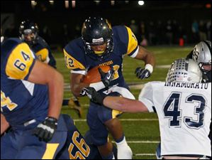 Whitmer's Tre Reditt-Sterrit finds a hole en route to a touchdown run.