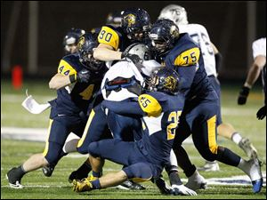 Whitmer High School players Jack Linch, 44, Jacob LaPoint, 90, Joe Nathan Mays, 75, and Austin Bly, 25, drop Hudson High School quarterback Mitchell Guadagni, 6, for a loss.