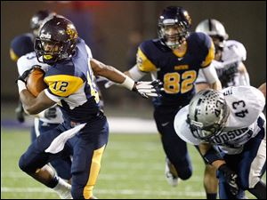 Whitmer High School player Tre Reditt-Sterrit, 12, spins away from Hudson High School player Mike Innamorato, 43, as he runs for a first down during the first quarter.