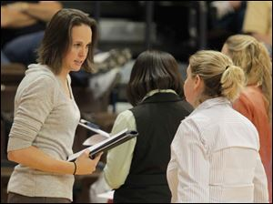 Former BGSU basketball standout and now assistant coach Ali Mann, left, speaks with head coach Jennifer Roos during a time out.
