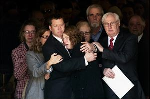 Jason Derkosh holds his wife, Elizabeth, at the funeral of their 2-year-old son, Maddox, who was killed Sunday after he fell from a wooden railing overlooking the painted dogs exhibit at the Pittsburgh Zoo and PPG Aquarium and bled to death after being mauled by the dogs.