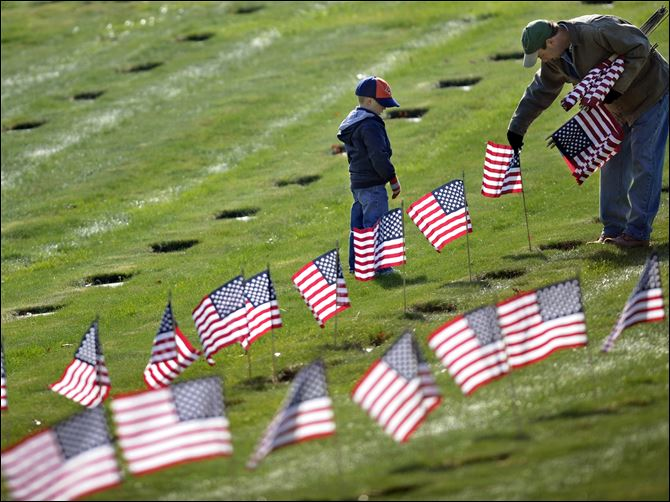 Joseph Manning, right, of Raynham, Mass., and his son Joey, 6, a Cub Scout, place U.S. flags at the graves of deceased veterans today at the National Cemetery in Bourne, Mass.