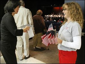 Jaymie Fontana, right, hands out a flag to pianist Bonnie Rowe before a special musical concert in honor of  Veterans Day.