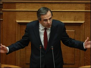 Greece's Prime Minister Antonis Samaras delivers a speech during a parliament meeting for vote on 2013 country's budget Sunday in Athens. The budget passed by a 167-128 vote in the 300-member Parliament.
