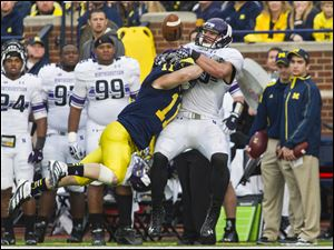 Michigan safety Jordan Kovacs (11) breaks up a pass intended for Northwestern tight end Dan Vitale.