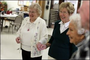 Donna Lapiarz, left, of Toledo and Gerry Braunfels, of Erie, Mi., laugh with each other about their mistakes while square dancing.
