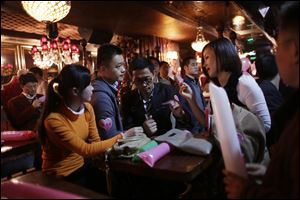 "Participants who are singles introduce themselves during a matchmaking party organized by one of the biggest Chinese matchmaking Web sites Sunday in Shanghai, China. The quirky holiday dubbed ""Singles Day"" that has grown into China's — and possibly the world's — busiest online shopping day. It is China's answer to Cyber Monday in the United States."