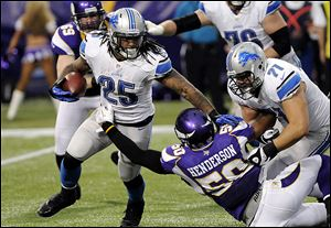 The Lions' Mikel Leshoure (25) gets a block from teammate Riley Reiff, right, as he tries to break a tackle by the Vikings' Erin Henderson, center, during the first half.