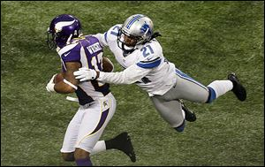Minnesota Vikings wide receiver Jarius Wright, left, tries to break a tackle by Detroit Lions cornerback Jacob Lacey.